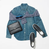Men`s clothing set. Male denim shirt, black sneakers, leather handbag and blue sunglasses Royalty Free Stock Images