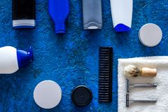 Men`s cosmetics for hair care and shaving. Shampoo, gel, razor, wax on blue background top view copyspace Royalty Free Stock Image