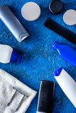 Men`s cosmetics for hair care and shaving. Shampoo, gel, razor, wax on blue background top view copyspace Stock Image