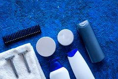 Men`s cosmetics for hair care and shaving. Shampoo, gel, razor, wax on blue background top view copyspace Stock Photos