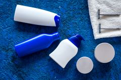 Men`s cosmetics for hair care and shaving. Shampoo, gel, razor, wax on blue background top view copyspace Stock Photography