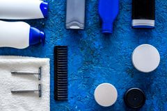 Men`s cosmetics for hair care and shaving. Shampoo, gel, razor, wax on blue background top view copyspace Royalty Free Stock Photos