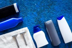 Men`s cosmetics for hair care and shaving. Shampoo, gel, razor, wax on blue background top view copyspace Stock Photo