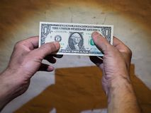 Men`s dirty hands holding a dollar paper bill royalty free stock images