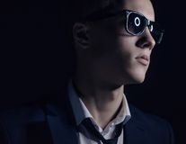 Men's fashion theme: handsome young man in a stylish suit and sunglasses standing on a dark background in the studio. Men's fashion theme: handsome young man in Royalty Free Stock Photos