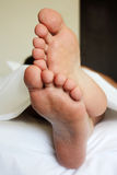 Men's feet. Under the blanket Royalty Free Stock Photography