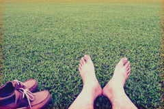 Men's feet ans shoes on the background of lush green grass ,vintage style Royalty Free Stock Image