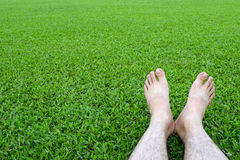 Men's feet on the background of lush green grass Royalty Free Stock Photography