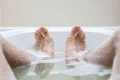 Men's feet in a bathtub, selective focus on toes Stock Photos