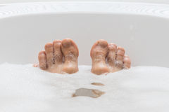 Men's feet in a bathtub, selective focus on toes Royalty Free Stock Photo