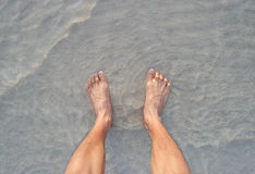 Men's feet on the beach. Royalty Free Stock Photo