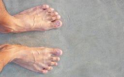 Men's feet on the beach. The Men's feet on the beach Stock Photo