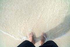 Men`s feet are on the beach. Men`s feet are standing on the beach with ocean waves Stock Photos