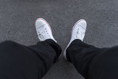 Men's feet in black trousers and white sneakers. On the pavement Royalty Free Stock Photography