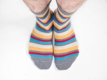 Men`s feet in funny, colorful socks. On a white background Royalty Free Stock Images