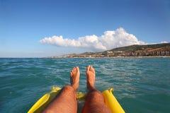 Men's feet on inflatable mattress, sea. Men's feet on yellow inflatable mattress, sea, far shore and beach Royalty Free Stock Images