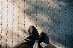 Men`s feet with jogging pants. On brick floor Stock Photos