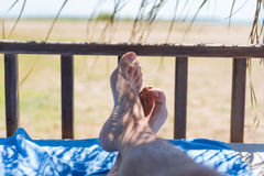 Men's feet on lounge in bungalow sea view. Men's feet on lounge with blue hotel towel first person view from bungalow Royalty Free Stock Photos