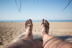 Men's feet on lounge in bungalow sea view. Men's feet on lounge first person view from bungalow on the sea with sand beach Stock Image