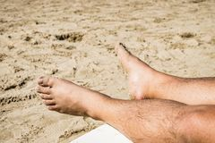 Men`s feet on lounge in sea view. stock photos