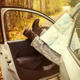 Men's feet with a map in the car. A man travels . Autumn. Men's feet with a map in the car. A man travels Stock Image