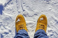 Men`s feet in orange boots and jeans in the snow. Cold weather lifestyle Stock Photography