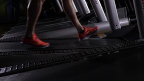 Men`s feet in red sneakers on the treadmill.