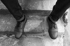 Men's feet  in retro shoes. Men's feet dressed in selvedge jeans and retro shoes Royalty Free Stock Photography