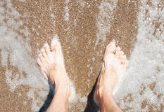 Men`s feet on the sand by the sea. Weekend conception Royalty Free Stock Photo