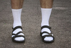 Men's feet in sandals. The lower part of men's feet in white socks and sandals Stock Photos