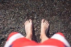 Men's feet on sea pebbles Royalty Free Stock Photos
