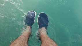 Men`s feet in the sea and in slippers stock footage