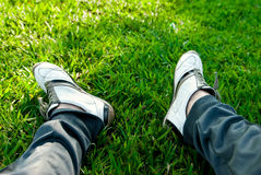 Men's feet in sneakers. Concept photo of resting. Men's feet in sneakers and Sport Pants on the green grass Royalty Free Stock Photos