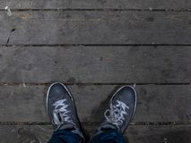 Men`s feet in sneakers stand on the wooden floor. Fashionable Men`s Sneakers royalty free stock photo