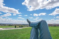 Men`s feet in socks on relaxation in park with blue sky. Men`s feet in socks on relaxation day in park with blue sky and clouds Stock Photos
