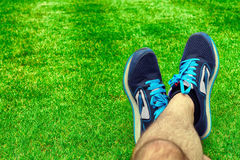 Men's feet in sports footwear. Foot football on the lawn close up Royalty Free Stock Photo