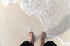 Men`s feet on the beach. Men`s feet are standing on the beach with ocean waves Royalty Free Stock Image