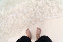 Men`s feet on the beach. Men`s feet are standing on the beach with ocean waves Stock Photography
