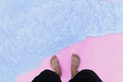 Men`s feet are standing on the beach Stock Photography