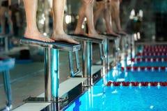Men`s feet standing on starting blocks preparing. To begin swimming race Royalty Free Stock Image