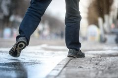 Men`s feet step over a puddle of spring in the city.  stock image
