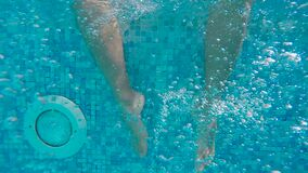 Men`s feet underwater. In the pool move stock footage