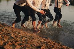 Men`s feet in the water. They are having fun, playing and splashing water around them. summer. Men`s feet in the water. men in costumes run on water. They are royalty free stock images