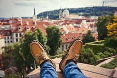 Men`s feet wearing brownleather shoes relaxing on the rooftop in old town. Of Prague Royalty Free Stock Photography