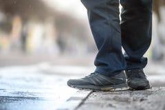 Men`s feet on the wet asphalt spring Stock Photo