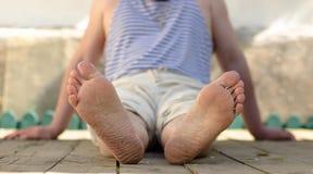 Men's feet on wooden legs Royalty Free Stock Photo