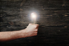 Men`s fist with luminous lightbulb on dark wooden background. The concept of bold ideas Stock Photos