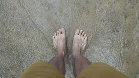 Men`s foot standing on waterfall stock video footage