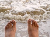 Men`s Foot  on the white sand near the sea. Vacation concept. selective focus Royalty Free Stock Images