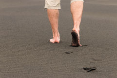Men's footprints in volcanic sand. Man walking barefoot across volcanic sand royalty free stock photography